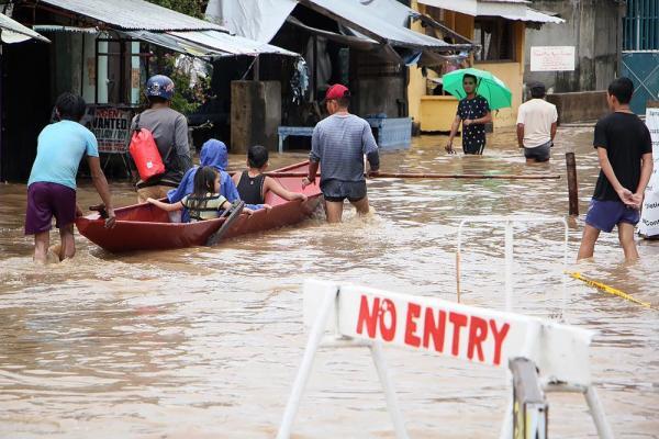 Rua inundada na cidade de Baao, nas Filipinas, após uma tempestade provocar inundações e deslizamentos. — Foto: Simvale Sayat/AFP