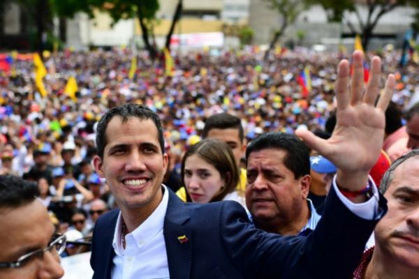 Líder da oposição venezuelana e autoproclamado presidente em exercício Juan Guaido acena durante uma manifestação em sua chegada em Caracas em (Foto: RONALDO SCHEMIDT / AFP)
