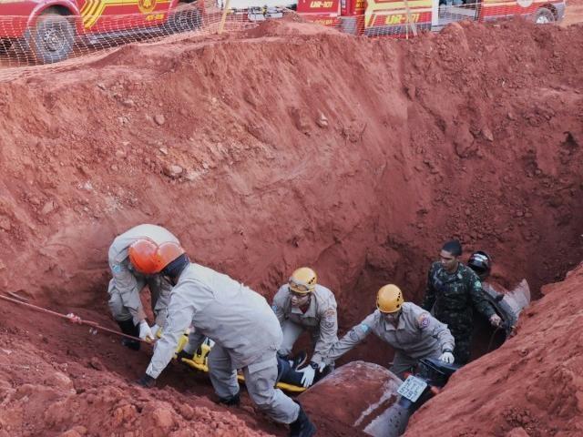 Piloto da motocicleta é retirado do buraco. (Foto: Henrique Kawaminami)