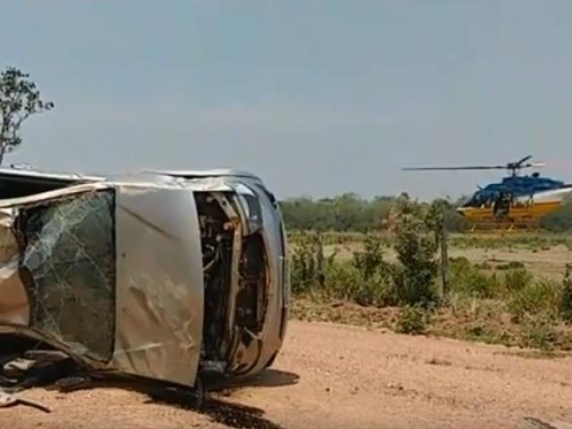 Camionete que capotou na estrada vicinal e ao fundo helicóptero usado no resgate as vítimas. - Crédito: (Divulgação/PRF)
