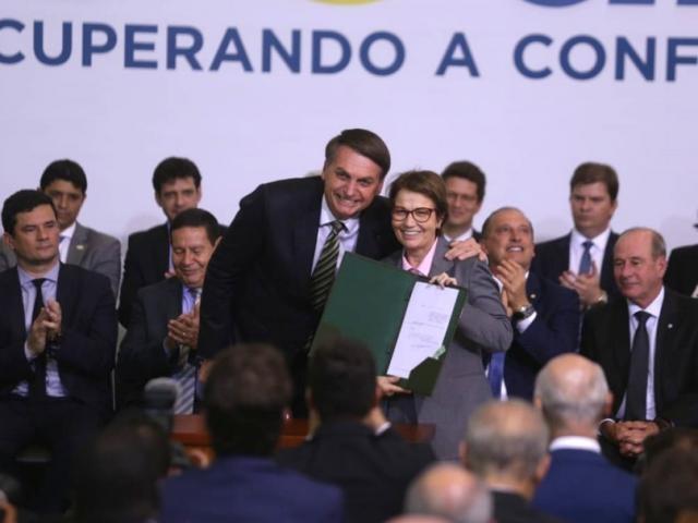 Bolsonaro e Tereza Cristina, em ato dos 300 dias de governo que apresentou decreto para o setor sucroalcooleiro; zoneamento da cana-de-açúcar foi derrubado. (Foto: Guilherme Martimon/Mapa)