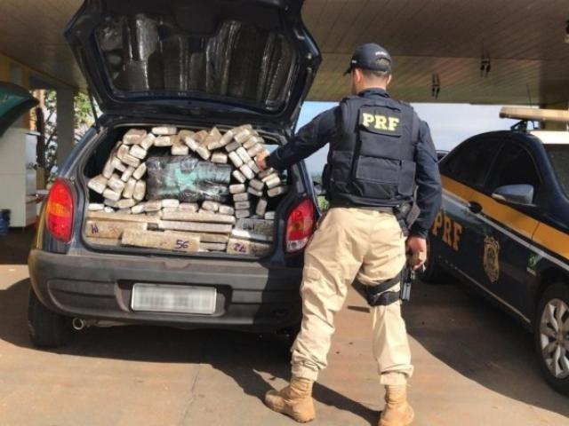 Policial contando a quantidade de tabletes de droga encontrados no porta-malas do veículo. - Crédito: (Divulgação/PRF)
