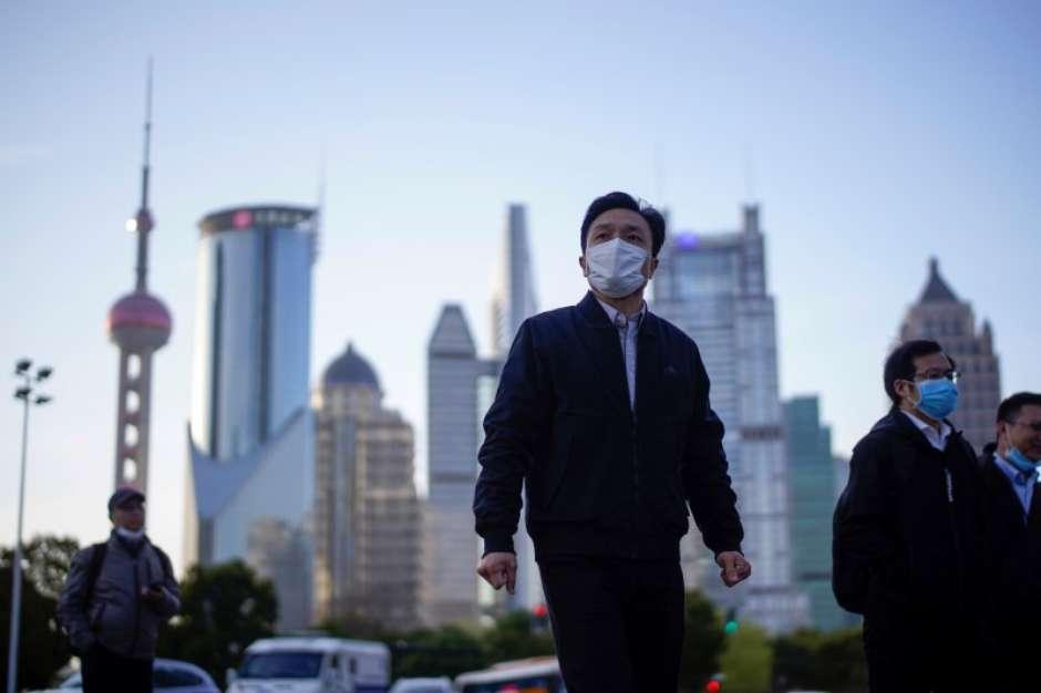 Pessoas com máscara de proteção no centro financeiro de Xangai 19/03/2020 REUTERS/Aly Song Foto: Reuters